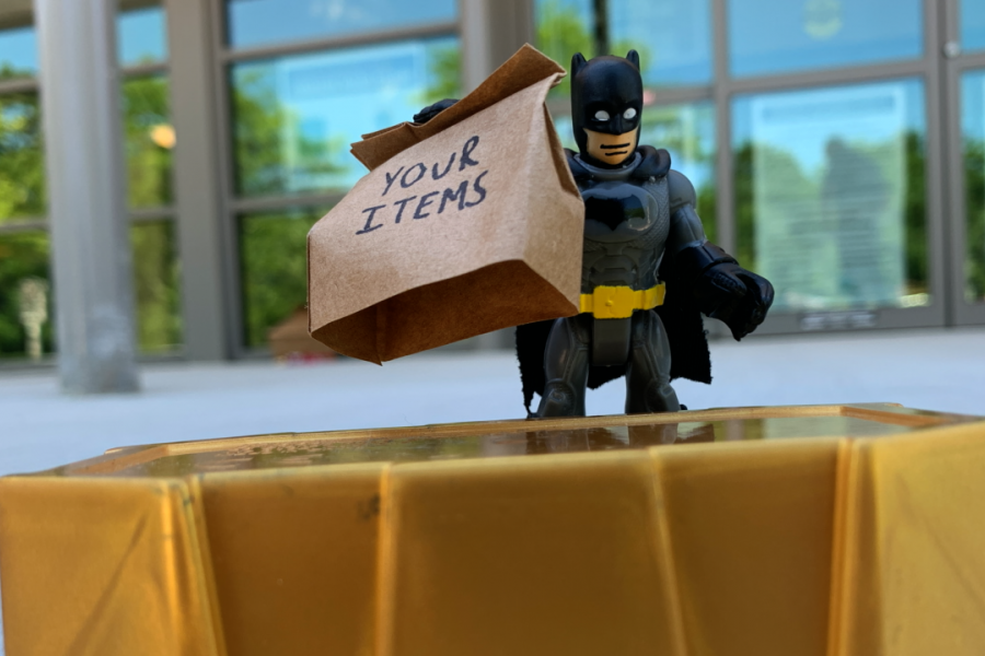 "Curbside Pickup linked image showing a batman figurine handing over a brown bag with the words ""Your Items"" written on the bag"